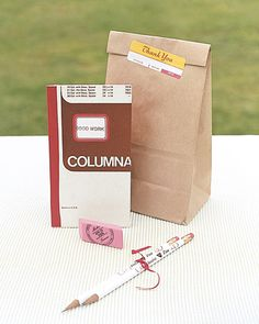 A brown paper favor bag contained custom school supplies including a handmade journal.