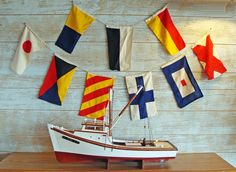 """A line of six colorful cotton stitched (not printed) nautical signal flags. Each signal flag measures approx. 9"""" X 16"""" and the line of six signal flags measures about 6 feet in length. The line of signal flags can be hung vertically or horizontally, perfect for decorating the nautical room, dress up your yacht and other coastal home applications. These are even suitable for framing!"""