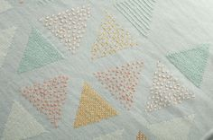 Close-up of PANDE TATU CUSHION hand embroidered by KISANY Living Linens for OTAGO design using exclusive Libeco Linen.