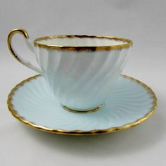 Tea cup and saucer made by Foley. Blue with a large bouquet of flowers on the inside rim of the tea cup. Heavy gold trimming on cup and saucer edges. Excellent condition (see photos). Markings read: Foley Bone China Made in England Please bear in mind that these are vintage items and