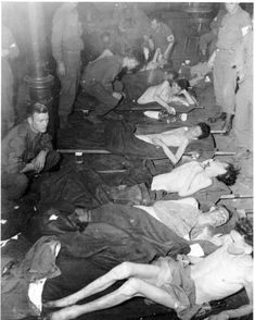 Lying on stretchers are some of the 63 emaciated American POWs liberated in Fuchsmuehl, Germany. From front to rear, the Berga survivors are: Pvt. Winfield Rosenberg, Lititz, PA; Pfc. Paul D. Capps, Herrin, IL; Pfc. James Watkins, Oakland, CA; Pfc. Joseph Guigno, Waltham, MA; and Pvt. Alvin L. Abrams, Philadelphia, PA.