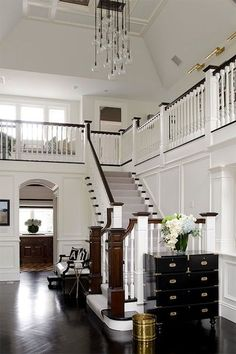 Two story foyer with white wainscotting.Wow! So traditional - but wait - look at the funky chandelier!! Love it!!!: