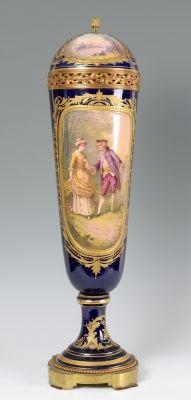 Jarrón. SÈVRES, Francia, siglo XIX. Porcelana esmaltada y bronce dorado. Escena firmada (Canelle). Con marca en el interior de la tapa. Medidas: 71 x 18 cm.