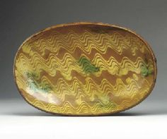 A GLAZED REDWARE LOAF DISH  Pennsylvania, 1775-1800  Oval, with coggle wheel rim, the interior with six-quill yellow slip decoration with green daubs 11½x7½ in.   Sold  26,290.~♥~