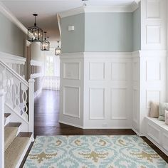 "Tall wainscoting and a window seat decorate the 2nd floor hallway of this custom residence in Louisville, KY.  The walls are painted #seasalt by @sherwinwilliams and the floors are 5"" hickory finished on site."
