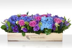 Purple and pink flowers in wooden trough