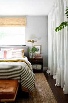 A bright and earthy bedroom with woven rug, stripped bedding, leather ottoman, and white curtains - Diy Interior Design Home Bedroom, Bedroom Decor, Budget Bedroom, Gray Bedroom, Calm Bedroom, Bedroom Ideas, Blinds For Bedroom, Serene Bedroom, Trendy Bedroom