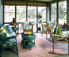 The sofa and coffee table were painted a deep, emerald green, which adds whimsy to the ensemble of naturally finished pieces. The colorful rug beneath the seating area echoes the woven texture of the furniture Outdoor Rooms, Outdoor Living, Outdoor Decor, Lakeside Living, Outdoor Seating, Coastal Living, Four Seasons Room, Outdoor Wicker Furniture, Sunroom Furniture