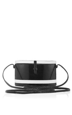 Designer Danielle Corona draws on experience at Valentino for her ultra-luxurious accessories crafted from the finest exotic skins. Finished with handmade Italian hardware, this **Hunting Season** trunk bag is crafted in black and white lizard leather for a strikingly chic accessory.