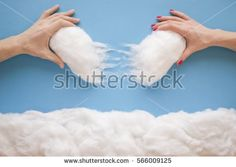 Two hands putting back a broken heart, in a heavenly scene with clouds and the heart made from cotton wool and a paper blue sky background.