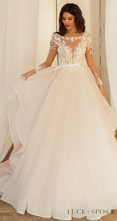 Colored blush ball gown wedding dress with long sleeves, lace bodice and layered tulle skirt design for the romantic bride | Princess style bridal gown | Luce Sposa Wedding Dresses 2021- Julia - Belle The Magazine See more gorgeous bridal gowns by clicking on the photo