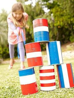 """Partygoers will have a blast with this July Fourth carnival game, crafted from tin cans. Known as the """"rocket toss,"""" each player gets three tries to knock over the pyramid. Let the games begin!"""