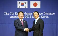 日韓財務対話で握手を交わす韓国の柳一鎬企画財政相(左)と麻生太郎財務相(8月27日、ソウル)=共同