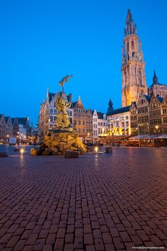 The Brabo statue fountain and the Church of Our Lady in Antwerp's Grote Markt square. Antwerp, Belgium