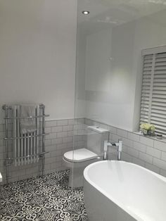 The clean white colour in this bathroom provides the perfect backdrop for that gorgeous 'boho' patterned tile floor.