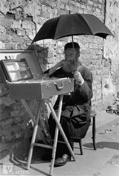 A Jewish vendor sitting on the street in the Warsaw ghetto shades himself with a large umbrella