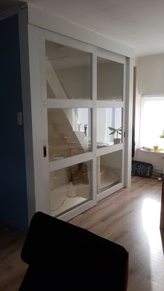 Op maat gemaakte schuifdeuren voor een open trap in een woonkamer. Deuren voorzien van veiligheids glas. Deze deuren worden speciaal op maat gemaakt voor elke type trap