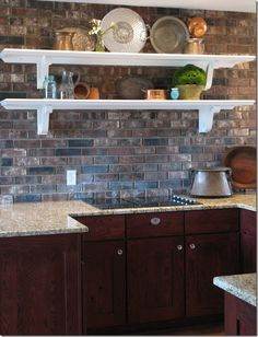 Love the brick kitchen wall and all the items on the shelves. #kitchen