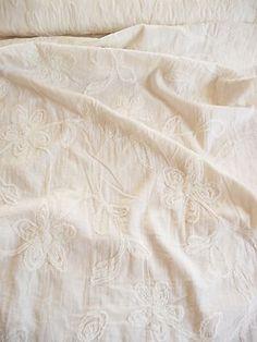 Reiner Baumwollstoff in creme. Auf den reinen Baumwollstoff wurden Blumen genäht.  Die Blumen bestehen aus einem ausgefransten Bändchen.  Wunderschön flippig.  Der reine Baumwollstoff ist herrlich leicht.  Die größte Blume ist ca. 13 cm hoch und ca. 12 cm breit.    Der reine Baumwollstoff liegt 140 cm breit und es sind noch 10 m vorhanden.      Aus diesem Stoff lassen sich Kleider, Blusen, Tuniken, Strandkleider, Röcke, Kissen,Gardinen, Hippikleider, Tischdecken und vieles mehr herstellen.