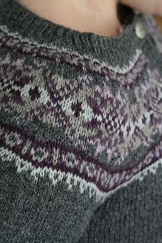 Knit seamlessly in the round from the bottom up, this simple, versatile, women's pullover/cardigan pattern features a classic XOXO stranded pattern in the 6-color yoke, with stars occupying the lozenge positions. The main color (charcoal) fades out to nearly white within the stranded pattern while, at the same time, a light purple darkens toward the center of the band. Hourglass waist shaping and fitted sleeves outline a flattering style to most sizes and shapes. The bottom band, button ...