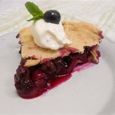 Strawberries, raspberries, and blueberries are piled into a homemade pie shell, covered with a flaky top crust, and baked until bubbly and golden brown.