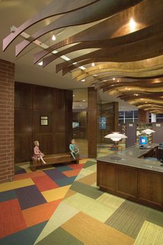 Patchwork Carpeting and Wooden Ceiling Decoration at Library Circulation Desk