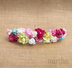 Tocado de flores de papel compuesto por una variedad de rosas, magnolias y otras flores de menor tamaño. Predomina el tono fucsia. Se puede adaptar a cinturón.
