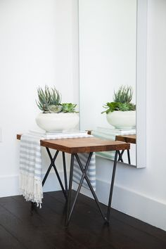 Modern foyer boasts an iron hairpin bench with wood top draped in a white and blue stripe throw blanket and a bowl of cacti placed in front of a wall hung mirror.
