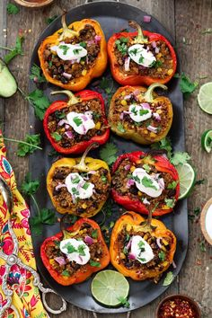 Vertical photo of 8 Quinoa Stuffed Peppers fully loaded with toppings.