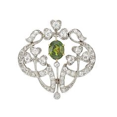 Belle Epoque Platinum, Gold, Demantoid Garnet and Diamond Pendant-Brooch  One oval demantoid garnet ap. 1.35 cts., 51 old-mine cut diamonds ap. 1.45 cts., c. 1905, ap. 5.8 dwts.