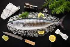 Photograph Tuna fish and ingredients on ice on a black stone table top view by Kamil Zab?ocki on 500px