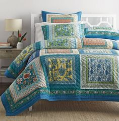 Garden Passage Quilt / Sham - This sunny patchwork quilt is an artful display of stylized florals framed with contrast patterning. Enlivened in vibrant shades of green, blue, teal, yellow, and flame, it's quilted by hand of pure cotton.
