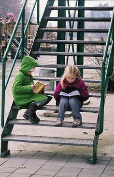 Two children read during recess on a cold January afternoon.