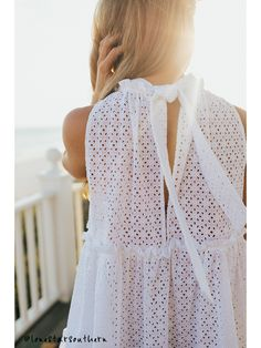 <u/>• Editor Notes:</u> This fresh loose feminine dress comes with sleeveless arms and a high neck which ties in a bow at the back. The dress falls to a mini length with two ruffle trimmed tiers. Cut for a loose fit this is ideal for pulling on over your swimmer and heading out for a beach or hotel lunch. <u/>• Additional Information:</u> · White broderie-anglaise cotton · High neck, sleeveless · Ruffle-trimmed band collar · Ruffle-tri...