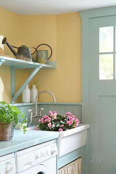 Turquoise mudroom features mustard yellow paint on upper walls and turquoise beadboard on lower walls lined with an enclosed washer and dryer as well as a white apron skirted sink under turquoise shelves.