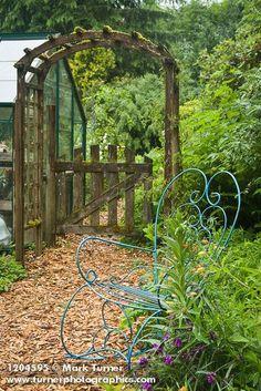 Blue wire chair, Spider Lily, Alstroemeria beside wood chip path leading to wooden arbor [Tradescantia 'Purple Profusion'; Alstroemeria aurea]. Kathy Hirdler, Mount Vernon, WA. © Mark Turner