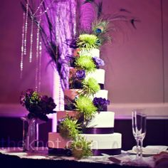 Green spider mums and purple lisianthus decorated the all-white cake tiers, topped with a few feathers.