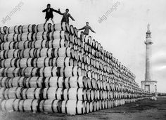 Three boys on a pile of herring barrels next to the Nelson monument in Yarmouth.  Photo, England, 30.10.1937.