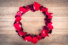 red roses leaves make a circle shape on wooden background