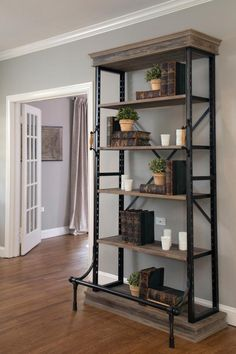 An industrial style wood and metal bookshelf displays old books, plants, and white glassware in the living room, as seen on HGTV's Fixer Upper.