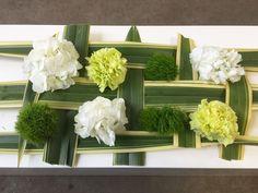 Auftrag: Blumendekoration für lange Tafel, alles in Grün-Weiß, Tischdekoration mit Blattgeflecht, Hortensie, Nelke und Orchidee