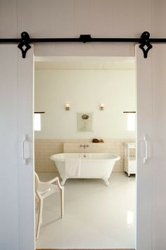 Even if your not interested in doors on tracks...go to her site...its awesome...her comments make for good reading..I like her style  White simple barn doors on a gorgeous track
