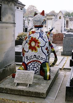"""Montparnasse Cemetery. Paris: Niki de Saint Phalle sculpture. Inscription: """"For our great friend, Ricardo. Dead too soon. Young, loved and beautiful"""". Niki de Saint Phalle and her husband created the well known Stravinski Fountain in front of Beaubourg. Ricardo Menon was her assistant who died of AIDS, there is a date of birth but no last name on the tomb ..one of the most original and creative at the cemetery."""