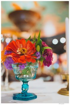 Colorful vintage glassware with brass accents make for beautiful eclectic centerpiece decor at a reception or party, complements of Farm and Filigree.