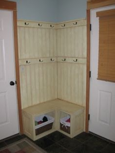 Corner Fix for a small mudroom: built-in bench with basket storage, double rack of coat hooks on beadboard.