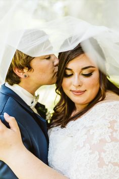 We love this special moment between these two brides! Megan Morales Photography captured this sweet kiss under the veil. This wedding was planned by Harmony Weddings and Events.