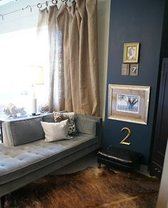 gray couch, black wall, dropcoth curtains, black and gold touches, cowhide rug, white pillows