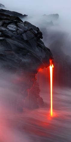 Its so cool. Molten rock spilling from a spout from of the edge of a small cliff. its just so unusual to see this, typically we see lava spewing from the tops of volcanoes or slowly flowing over the top of land.