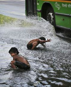 A bus splashes Indian children from a nearby slum as they cool off in water after a water main break on a street in New Delhi, India. (Kevin Frayer, AP)