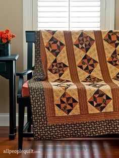 Halloween hues and striped sashing set the tone for a scrappy quilt composed  of…